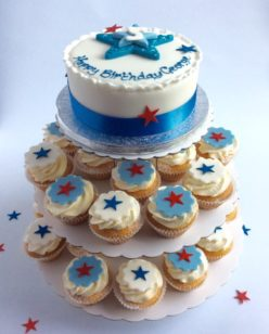 Round cake and cupcakes on stand with star decoration in blue