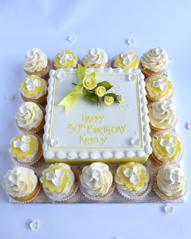cake and cup cakes with yellow flower spray