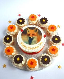round cake with cupcakes and animal photo topper