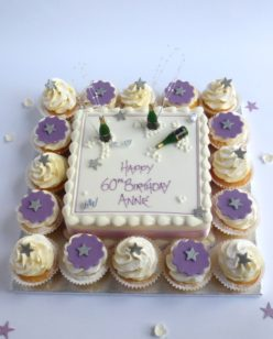 Cake with cupcakes and champagne bottle candles