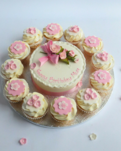 round cake and cupcakes with pink flower