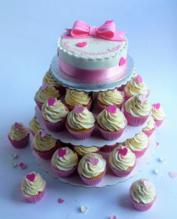 Round cake with cupcakes on stand with bow decoration