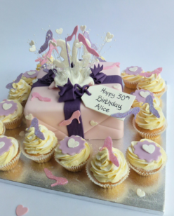 Pink cake with cupcakes and shoe decorations