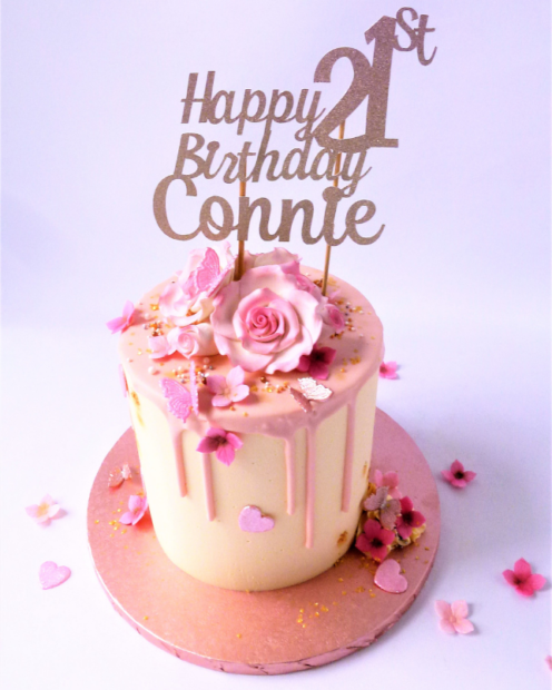 Pastel pink drip cake with topper