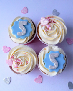 Cupcakes with icing glittered number, heart and sprinkle decorations