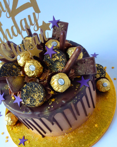Chocolate drip cake with cookies and chocolates