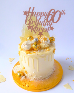 White chocolate cake with drip and happy birthday cake topper