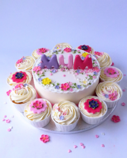 Colourful mothers day cake with cupcakes around