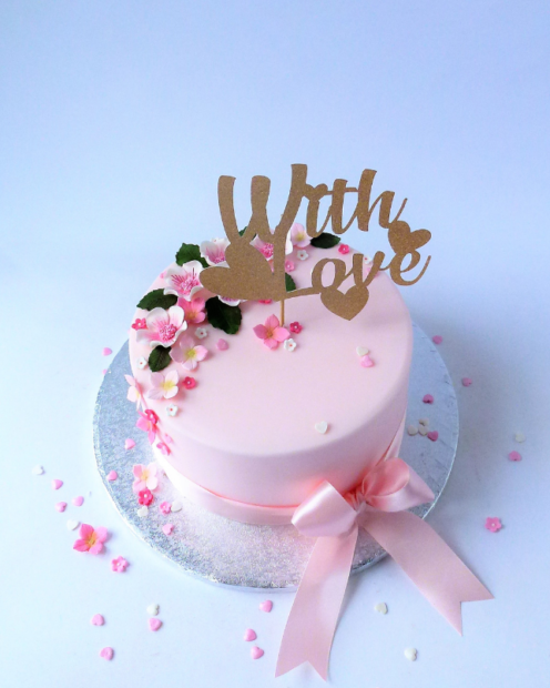 With love cake topper on a pink cake